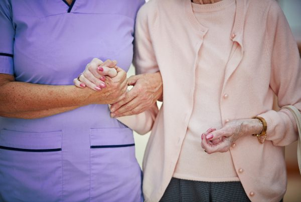 Carer holding hands with elderly person
