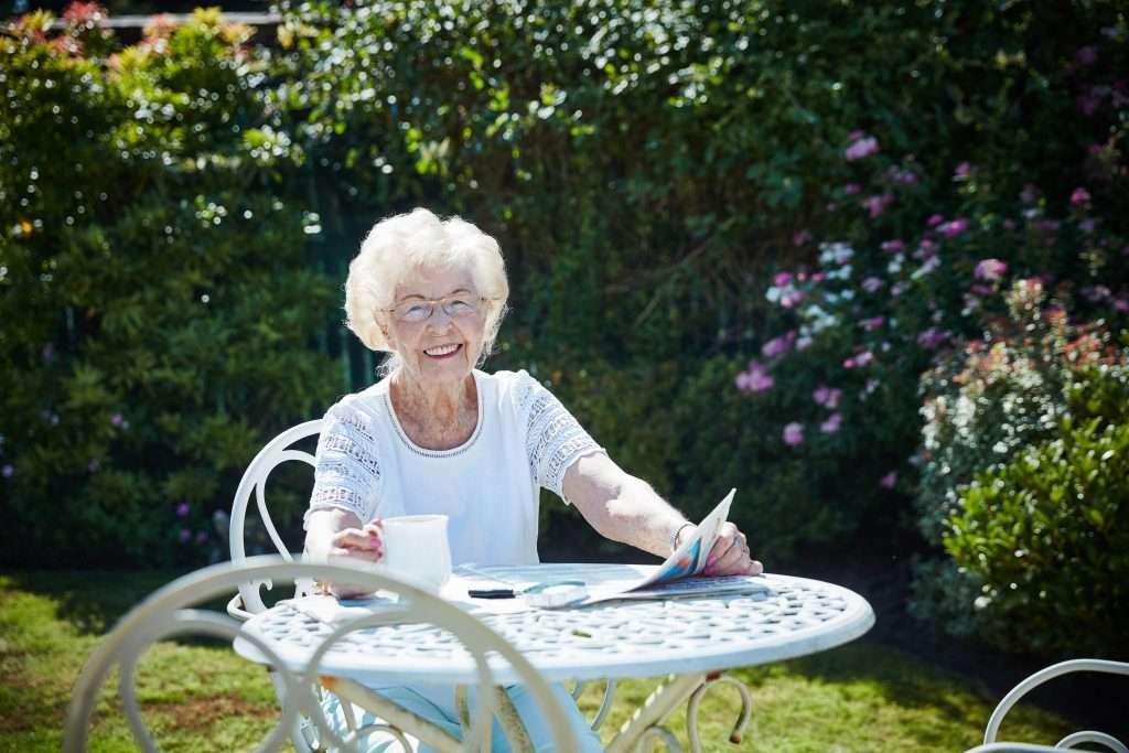 Elderly lady in garden reading newspaper