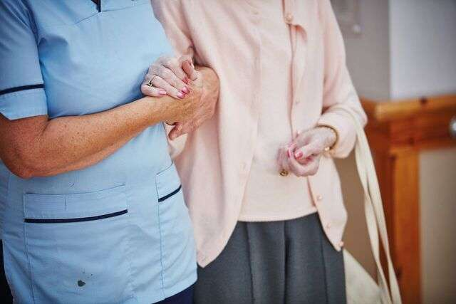 Carer holding hands with elderly resident at care home in Edinburgh