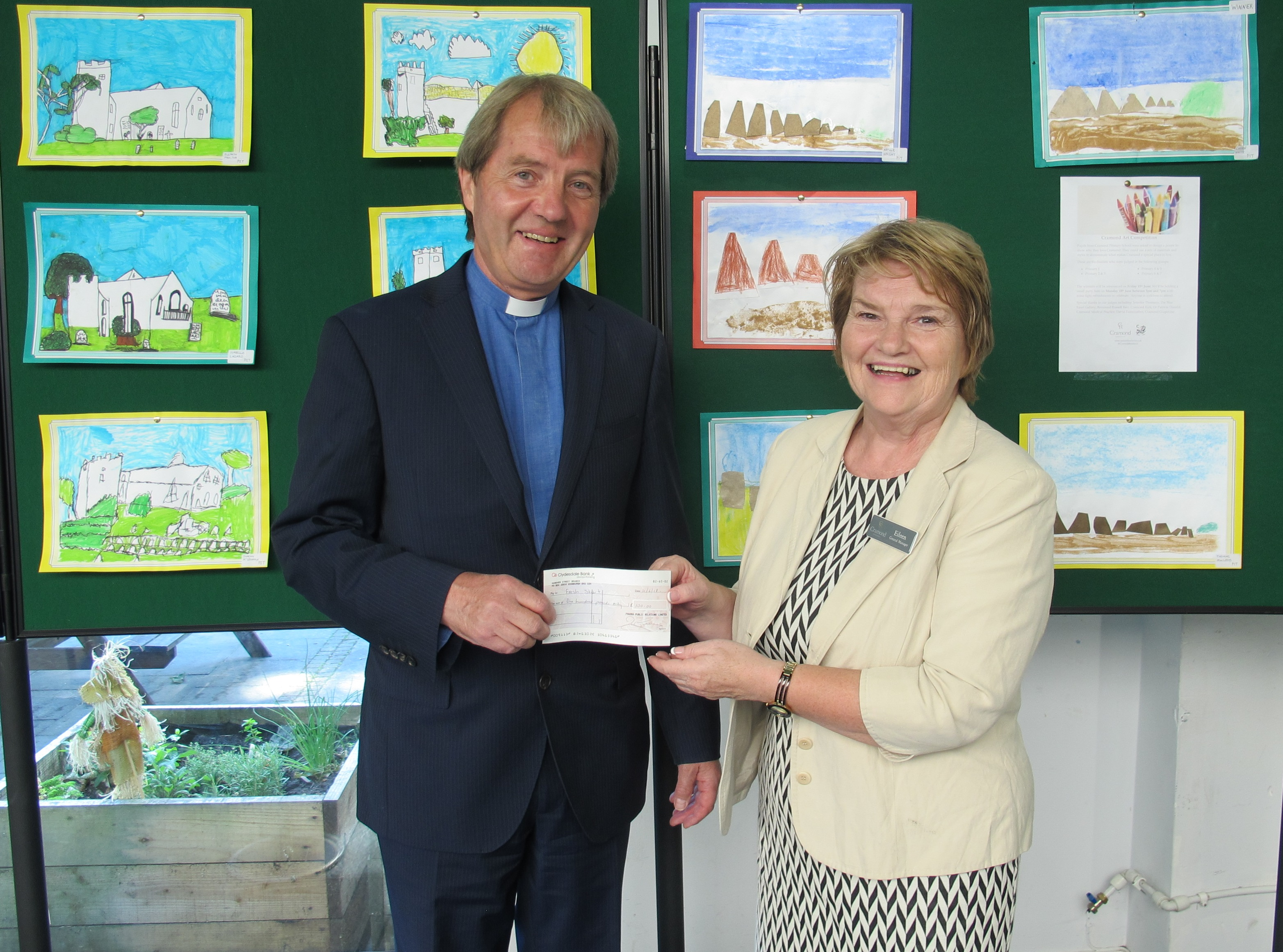 Eileen Gray, general manager at Cramond Residence handing donation to Russell Barr from Cramond Kirk