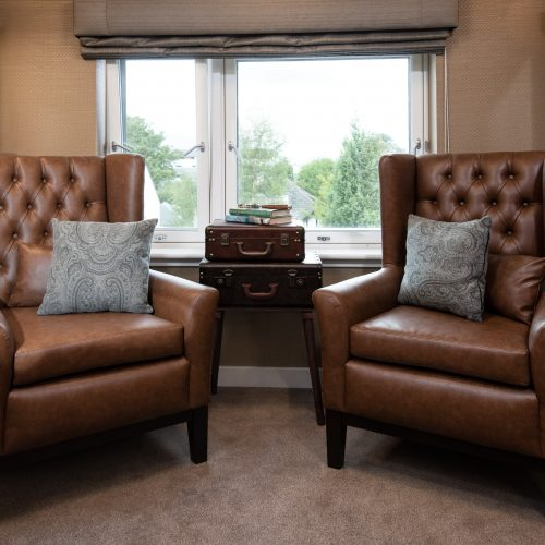 Snug with two chairs and suitcase decoration at care home