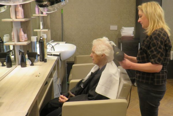 hairdresser from campbell young at cramond residence care home blow drying hair of a resident in seat