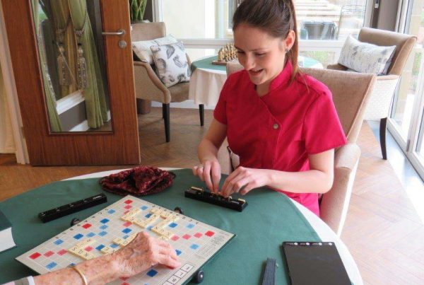 Lifestyle Coordinator playing scrabble with resident at care home in Edinburgh ahead of Spring Recruitment day