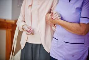 Care worker linking arms with resident