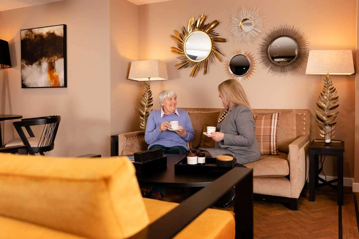 Residents having tea with staff in care home