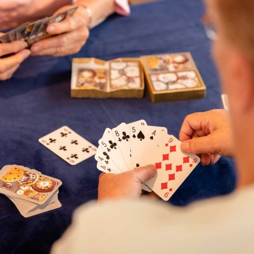 Residents playing cards in care home