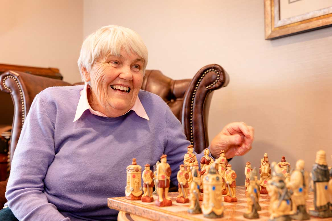 Resident smiling playing chess