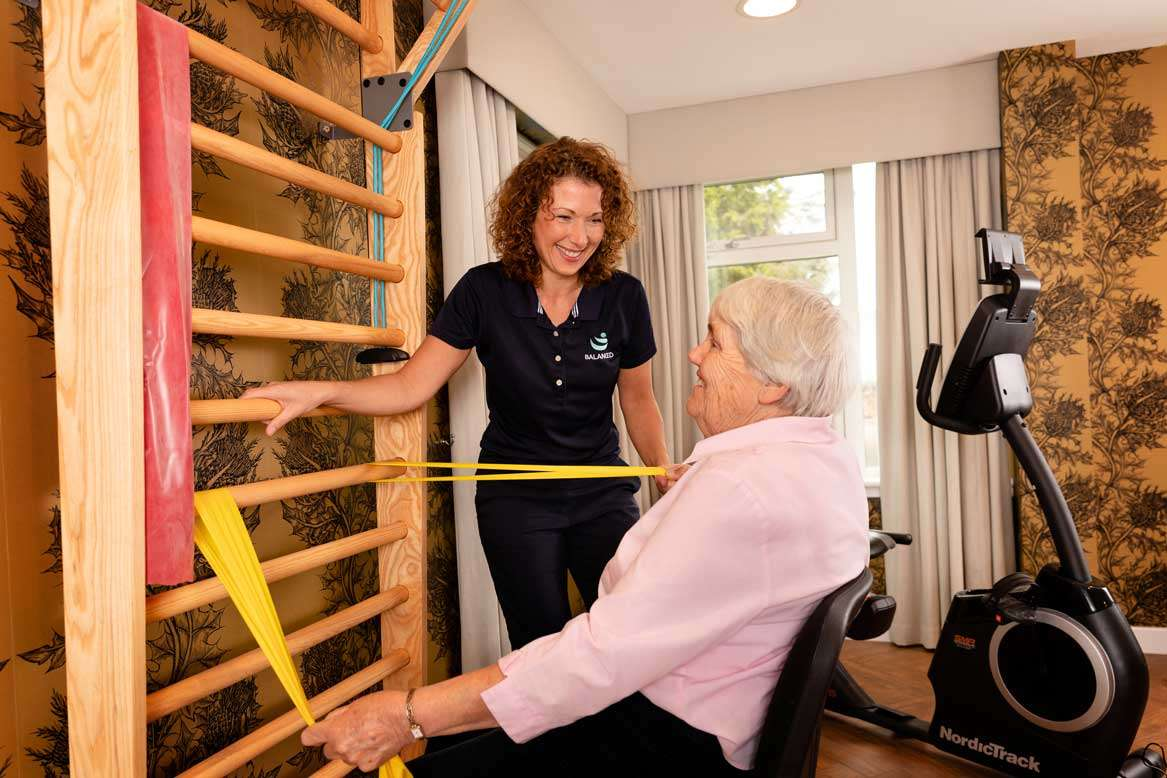 Resident exercising in gym with physio