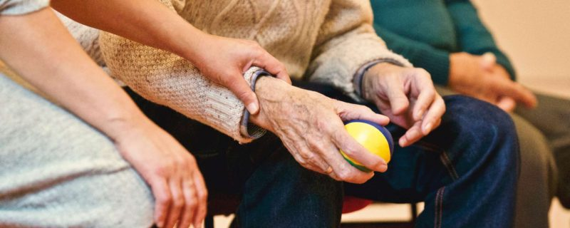 young holding arm of elderly man