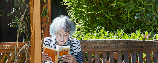 A resident reading their book in the garden
