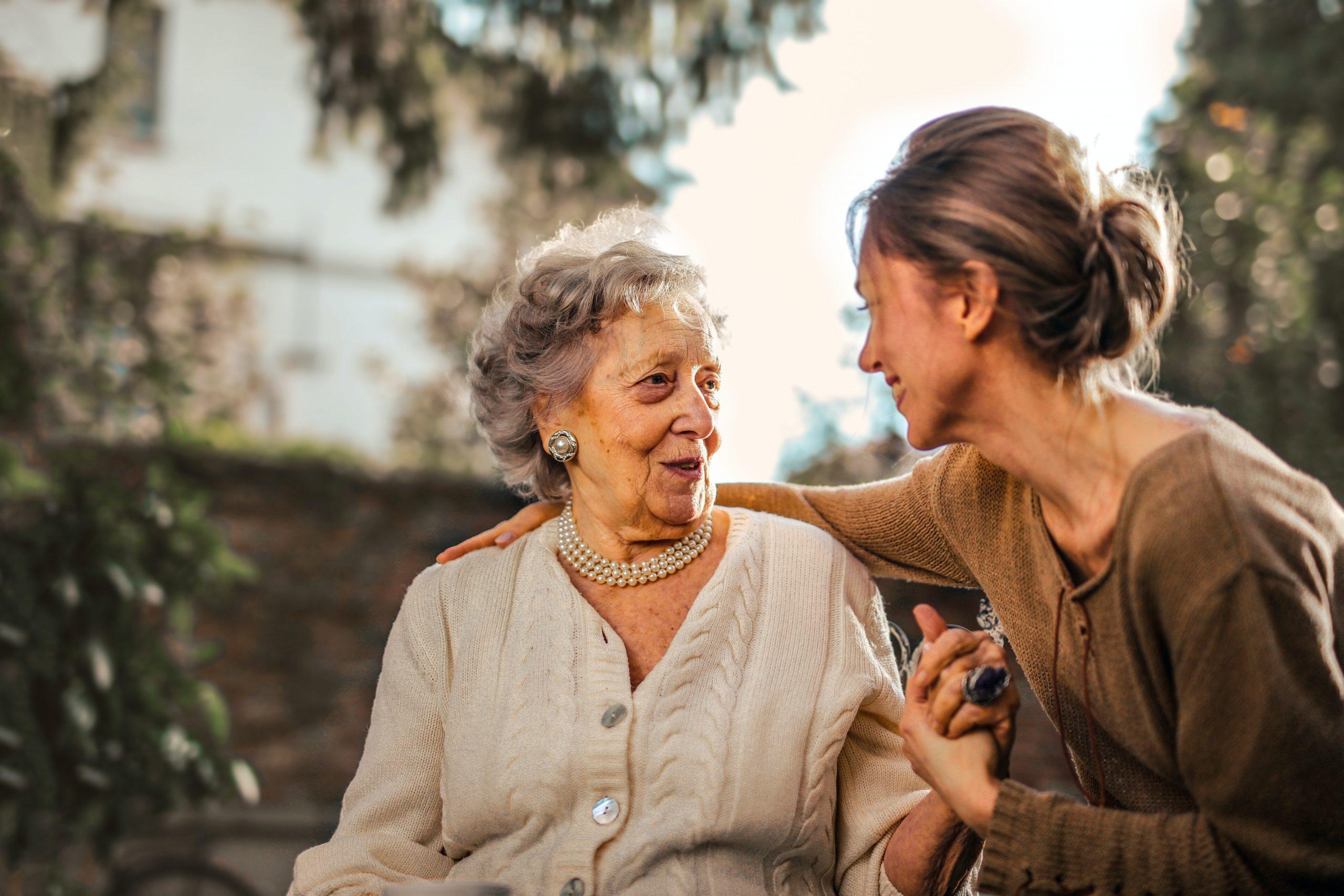 Women providing comfort to elderly woman