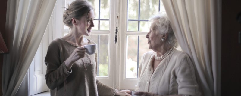 Young woman talks to elderly woman while drinking tea